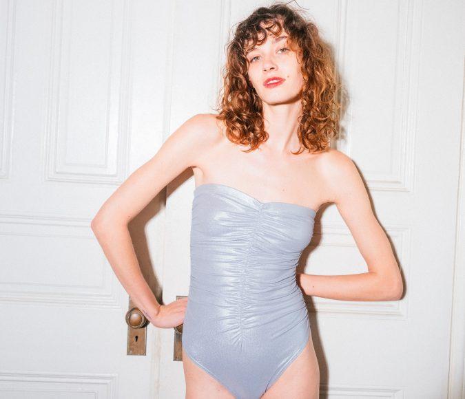Brunette model standing in front of a door in Karla Colletto Autumn Winter 2022 swimsuit.