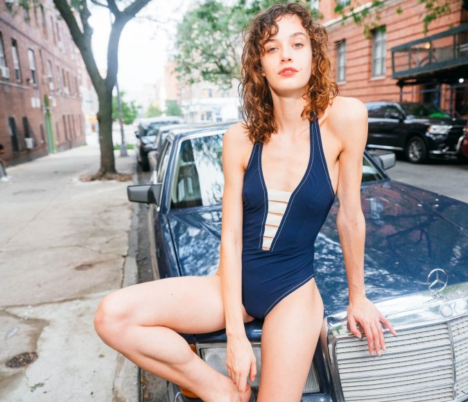 Brunette model lounging on the hood of a blue car in Cora Karla Colletto Autumn Winter 2022 swimsuit.
